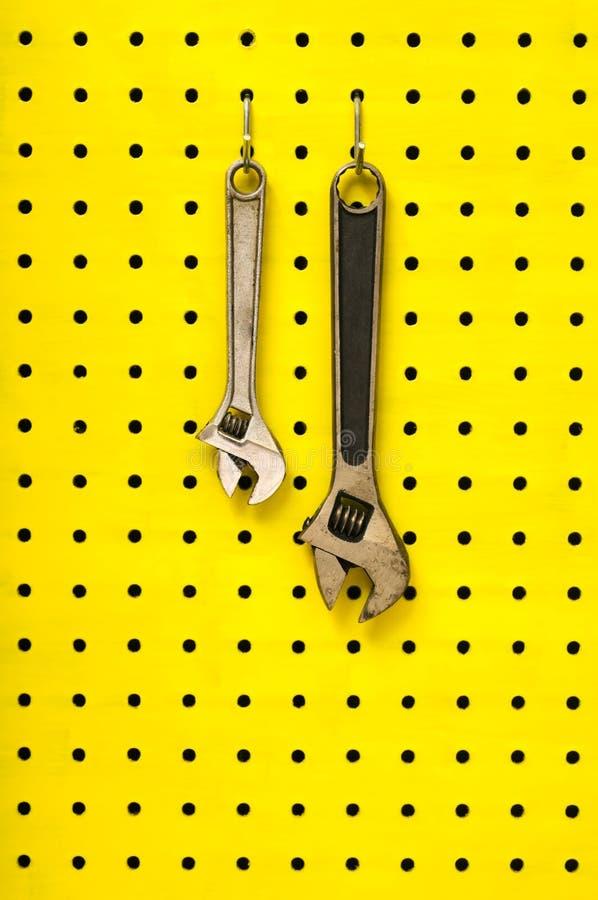 Coup de deux clés des crochets sur le pegboard jaune photographie stock libre de droits