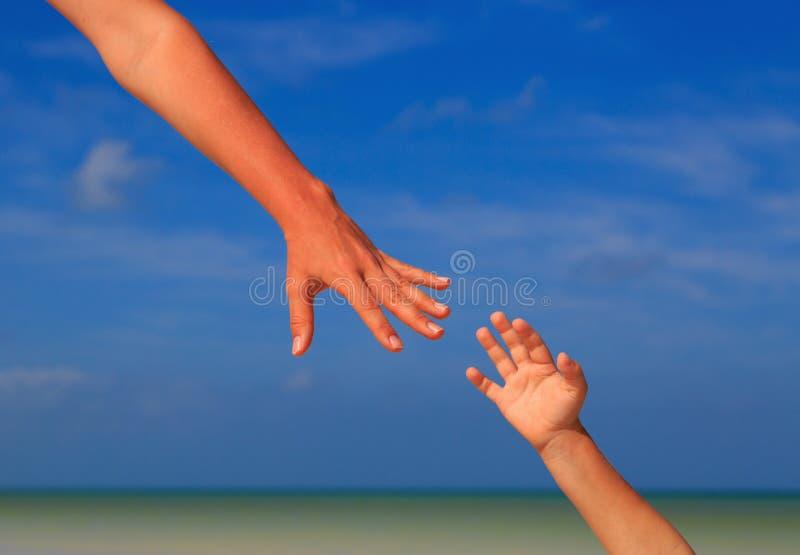 Coup de main de mère et d'enfant sur le ciel à la mer photo libre de droits