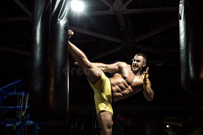 Coup-de-pied thaïlandais de poinçon de boxeur par le sac de sable photos stock
