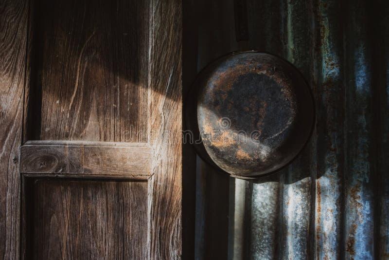 Coup rouillé de vaisselle de cuisine sur le mur de zinc avec l'éclat léger par la fenêtre en bois photographie stock