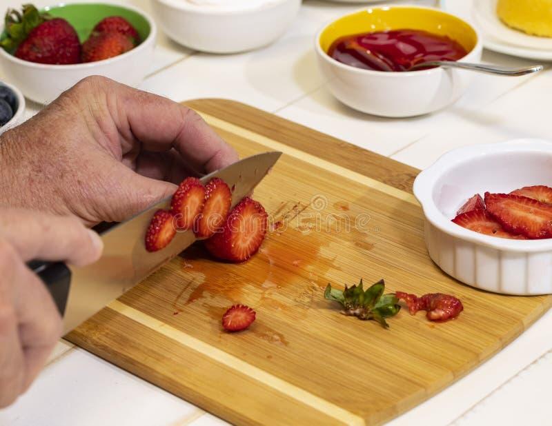 Coupant en tranches les fraises fraîches sur la planche à découper III photo libre de droits