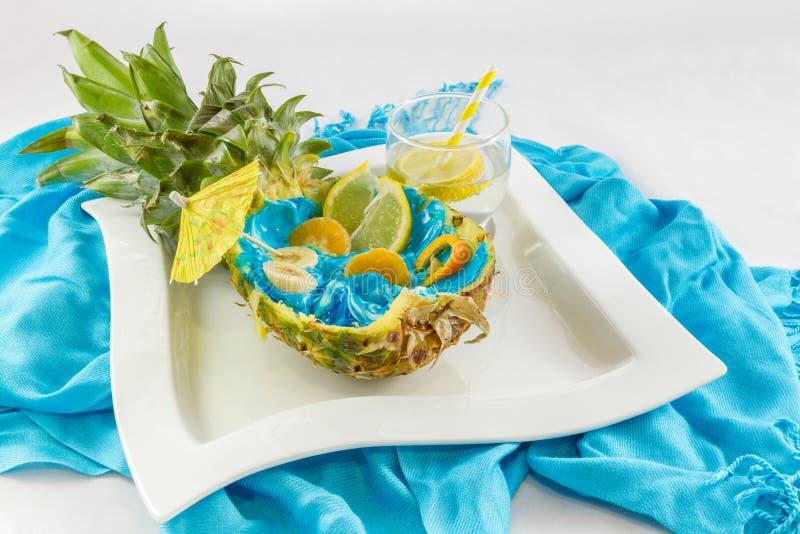 Coupe d'ananas dans la moitié avec le côté découpé en tranches de coctail de fruit et de citron v images libres de droits
