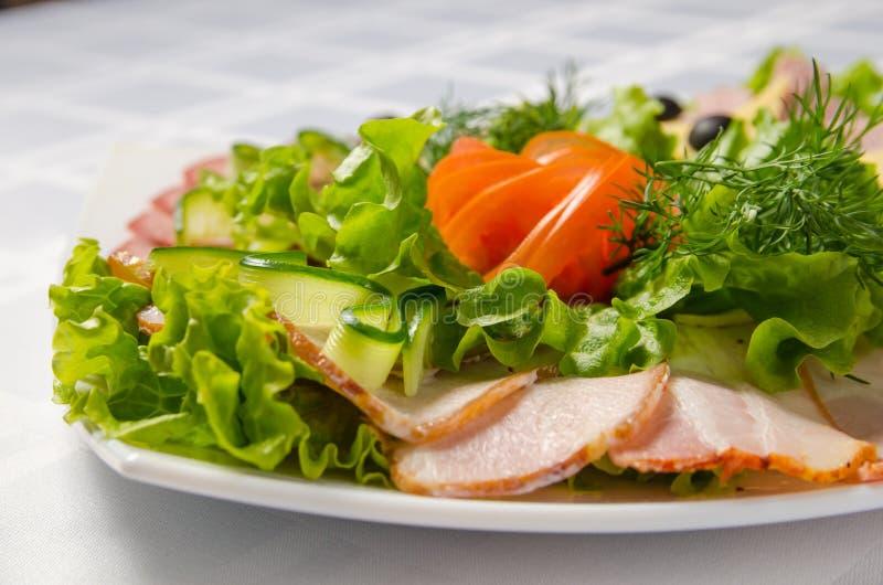 Coupe de banquet avec du jambon, les délicatesses de viande, le fromage, la saucisse fumée, l'olive, la laitue et la tomate sur l image stock