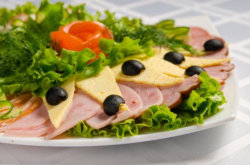 Coupe de banquet avec du jambon, les délicatesses de viande, le fromage, la saucisse fumée, l'olive, la laitue et la tomate sur l image libre de droits