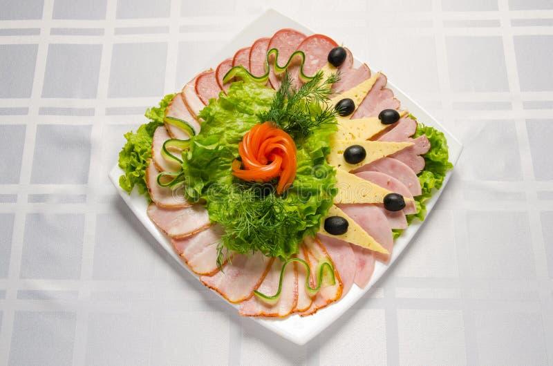 Coupe de banquet avec du jambon, les délicatesses de viande, le fromage, la saucisse fumée, l'olive, la laitue et la tomate sur l photo stock