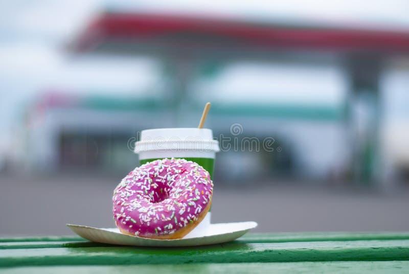 Coupe de café avec donut rose sur fond de station-service. Le petit déjeuner est en route photos libres de droits