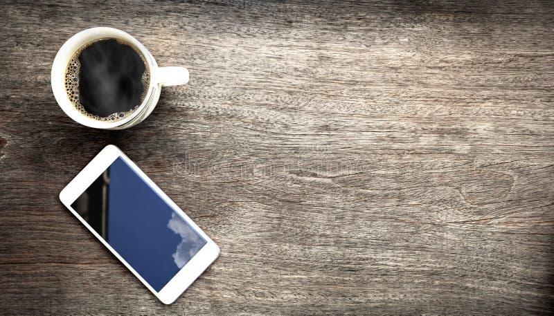 Coupe de café et téléphone portable sur table en bois images libres de droits