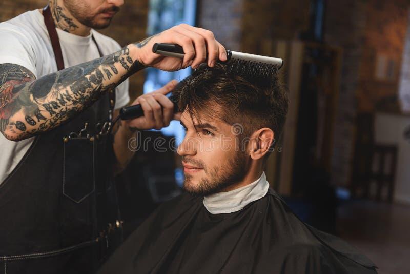 Coupe de cheveux de obtention macho élégante photos libres de droits