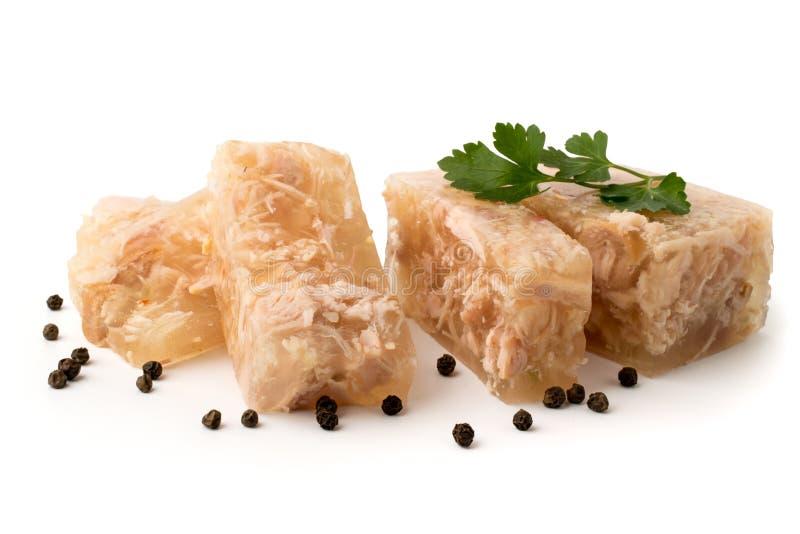 Coupe de gelée de viande dans les tranches avec les feuilles de persil et le poivre noir sur un blanc, plan rapproché images stock