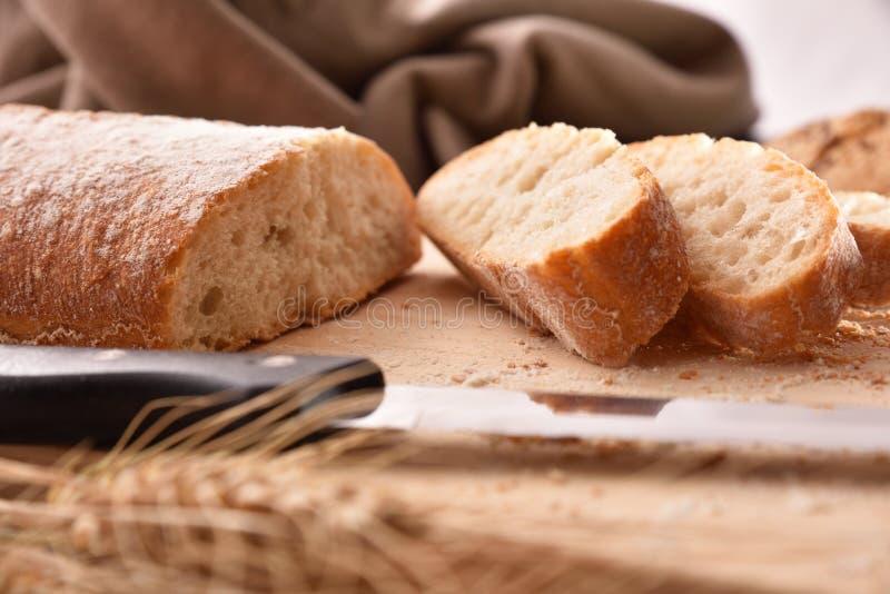 Coupe de pain en tranches sur la fin de planche à découper  photo libre de droits