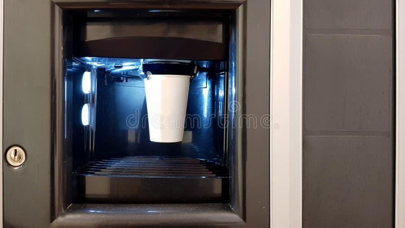 Coupe de papier blanc dans la fenêtre d'une machine à café Le processus de fabrication du café dans une machine à patauger photo stock
