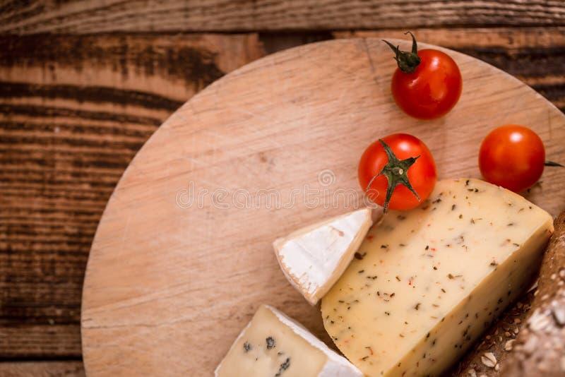 Coupe différente de fromage d'un plat en bois images libres de droits