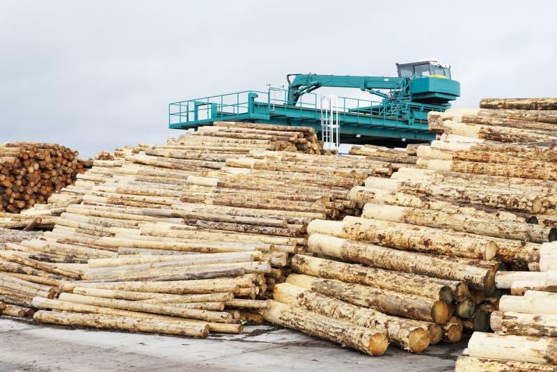 Coupe en bois de rondins de scierie l'écorce étant coupée empilée en vente avec des machines à l'arrière-plan photos stock