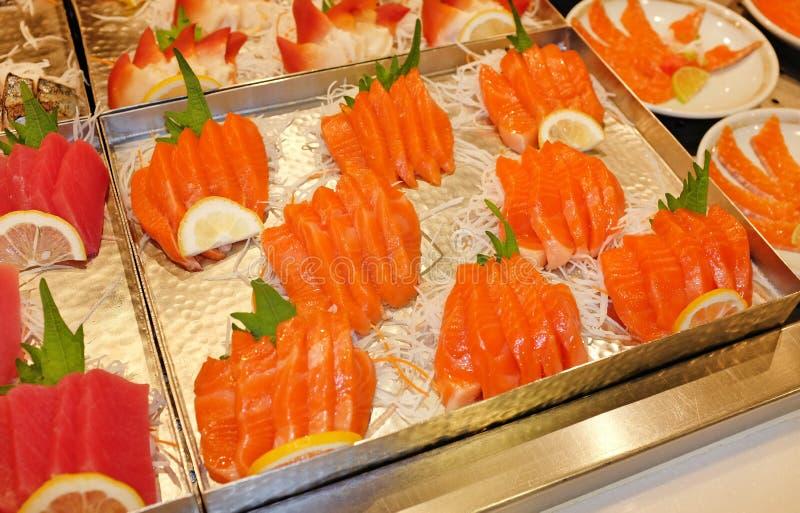 Coupe en tranches le sashimi saumoné sur le plateau photographie stock