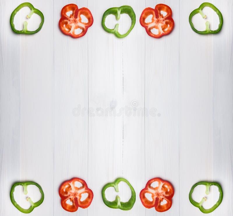 Coupe fraîche verte et rouge de paprika ou de poivron en tranches minces d'isolement sur le fond blanc images stock