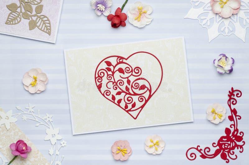 Coupe rouge de coeur de papier sur une carte de voeux avec les fleurs de papier photos libres de droits