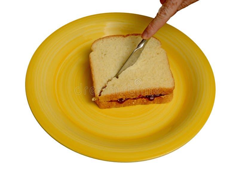 Couper en tranches le beurre d'arachide et le sandwich à gelée d'un plat jaune photo stock