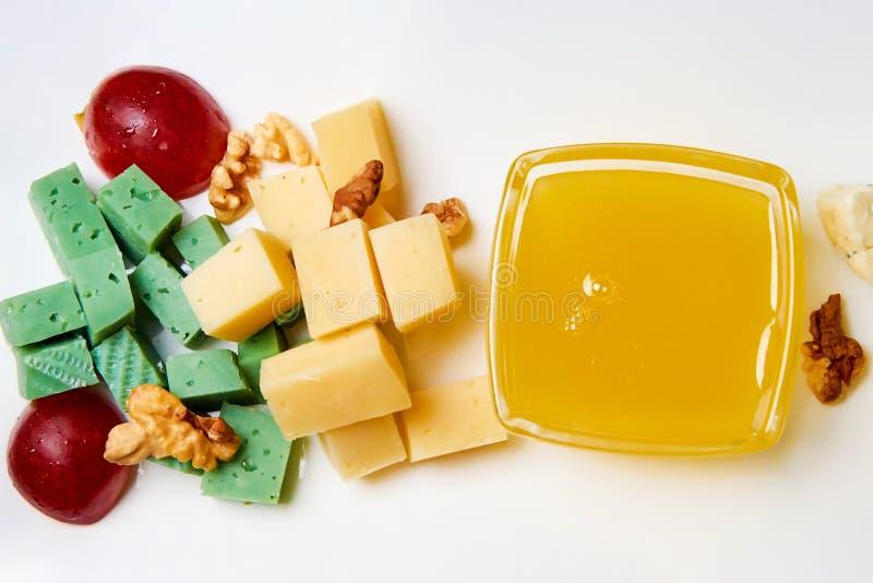 Couper en tranches le fromage avec des écrous, des raisins et le miel d'un plat blanc image stock