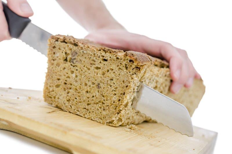 Couper un pain fait maison sur un panneau en bois photographie stock