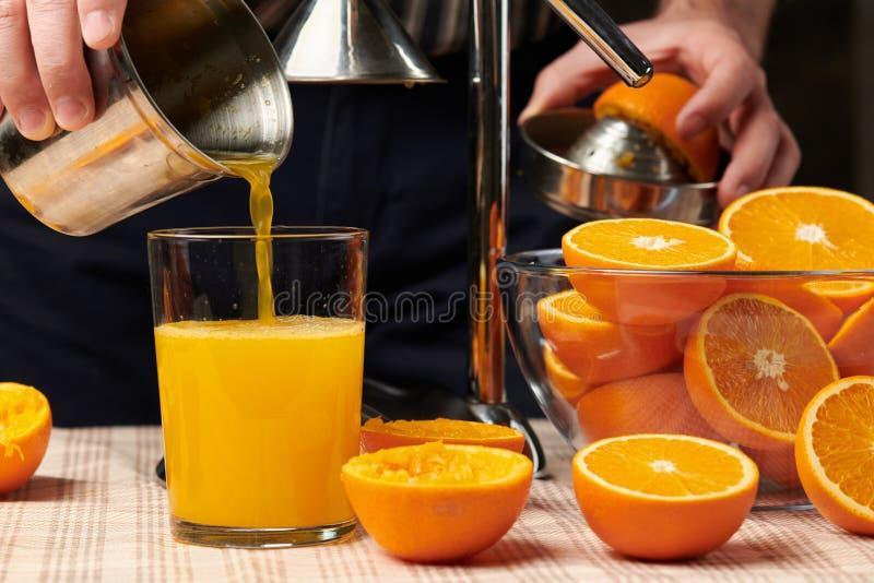Couper une orange avec une presse manuelle, fermer la vue, faire un verre de fraîcheur Oranges fraîches sur une table en bois, en image libre de droits
