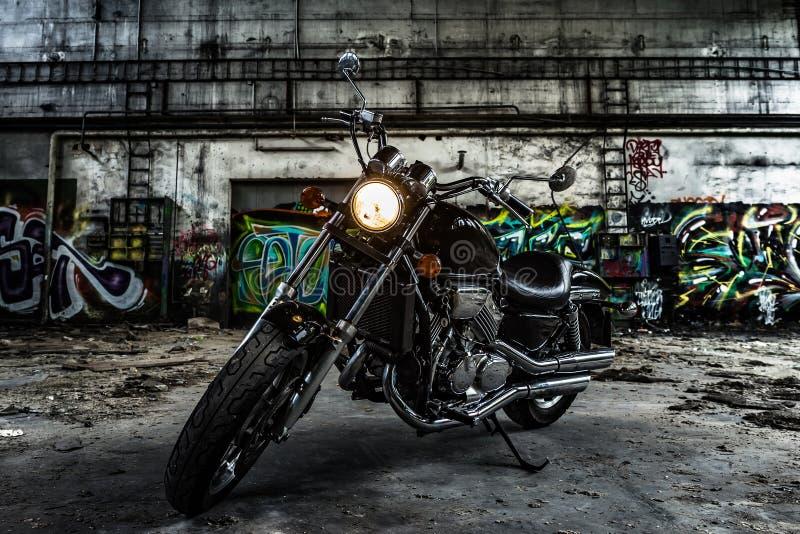 Couperet de moto dans un vieux hall industriel avec le graffiti urbain photographie stock libre de droits