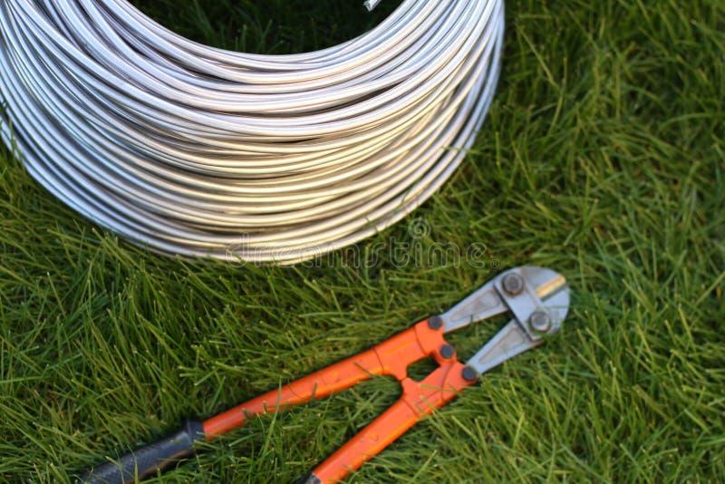Coupeur de boulon près du fil de bobine sur l'herbe Outil, technologie images stock
