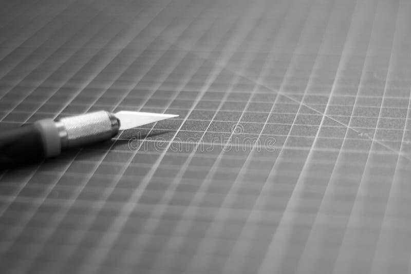 Coupeur de papier sur le tapis de coupe images stock