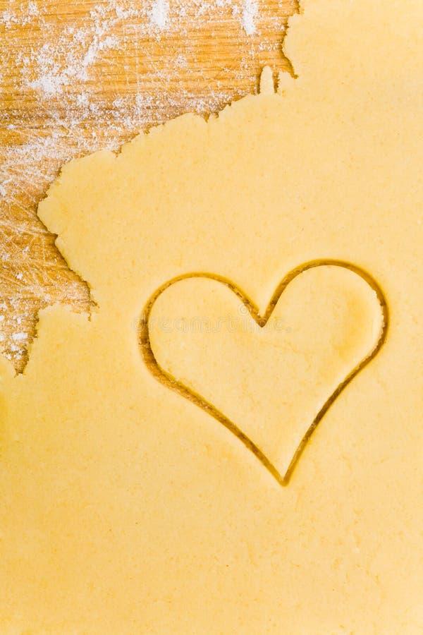 Coupeur en forme de coeur de biscuit sur la pâte photographie stock libre de droits