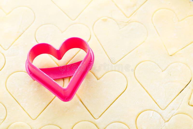 Coupeur en forme de coeur de biscuit sur la pâte crue images libres de droits