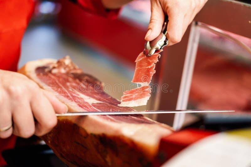 Coupeur professionnel découpant des tranches d'un serrano avec os entier photo libre de droits