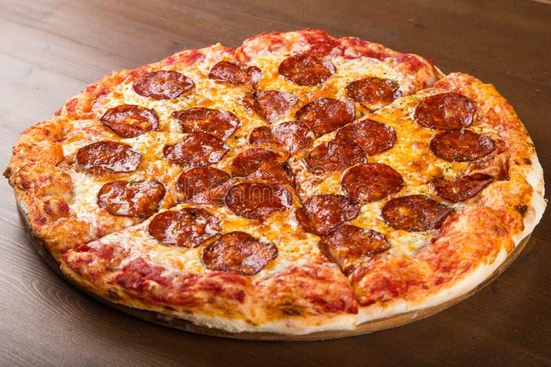 Coupez en morceaux de saucisse et de fromage de pizza sur un plateau en bois images libres de droits