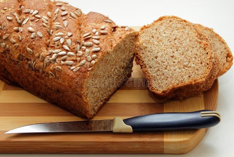 Coupez en tranches de pain de son, arrosées avec des graines de tournesol images libres de droits