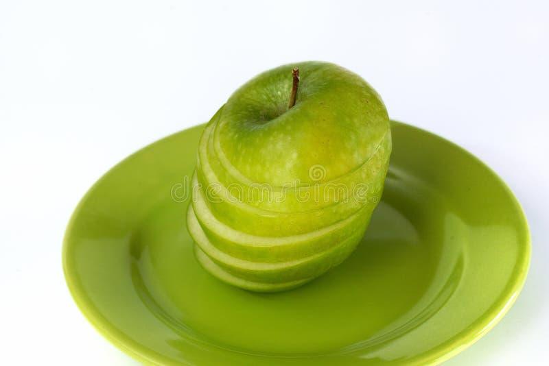 Coupez la pomme verte d'une plaque photographie stock libre de droits