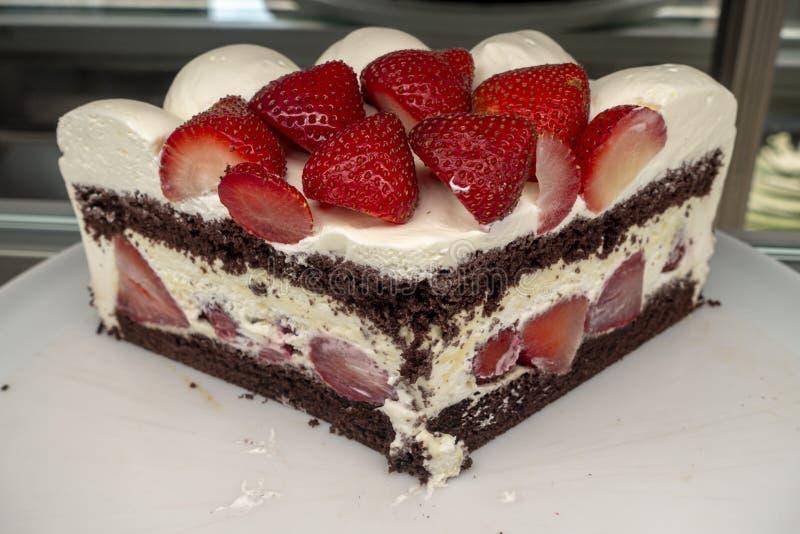 Coupez la tarte sablée de fraise avec de vraies fraises blanches et la mise en couches brun chocolat photos libres de droits