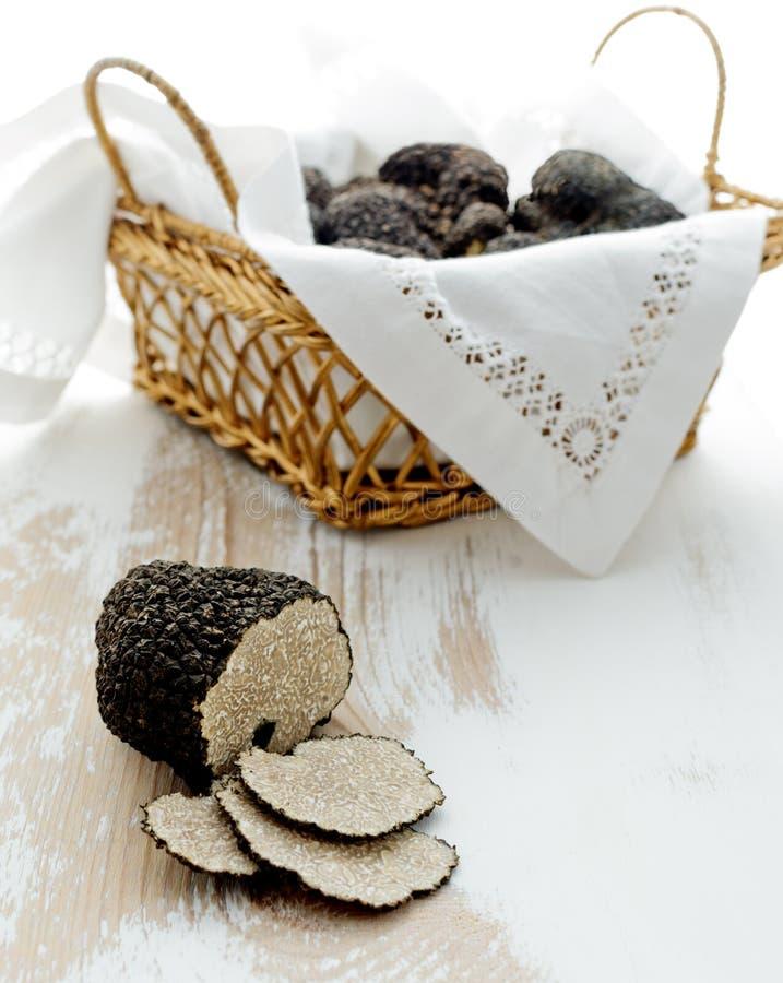 Coupez la truffe noire sur la vieille table photos stock