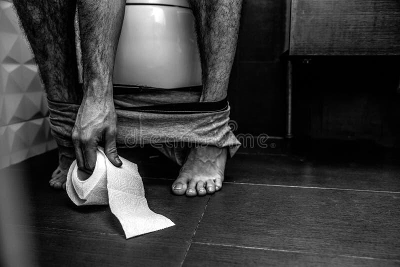 Coupez la vue de l'image arrière et blanche L'homme s'asseyent sur la toilette et atteignent le papier Les jambes sont minces et  photos stock