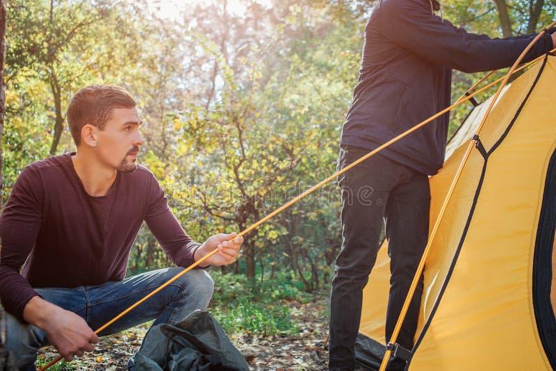 Coupez la vue de travailler de deux hommes Tient d'abord la corde tandis qu'une autre tente de contacts Ils sont dans la forêt photographie stock libre de droits