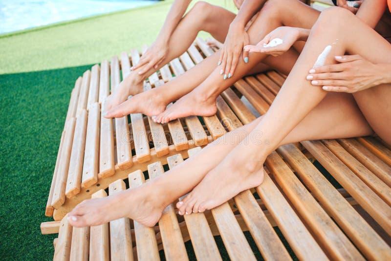 Coupez la vue des jambes minces et de bien-construction de jeunes femmes du ` s Ils ont bronzage Les mains ont mis de la lotion d photo libre de droits
