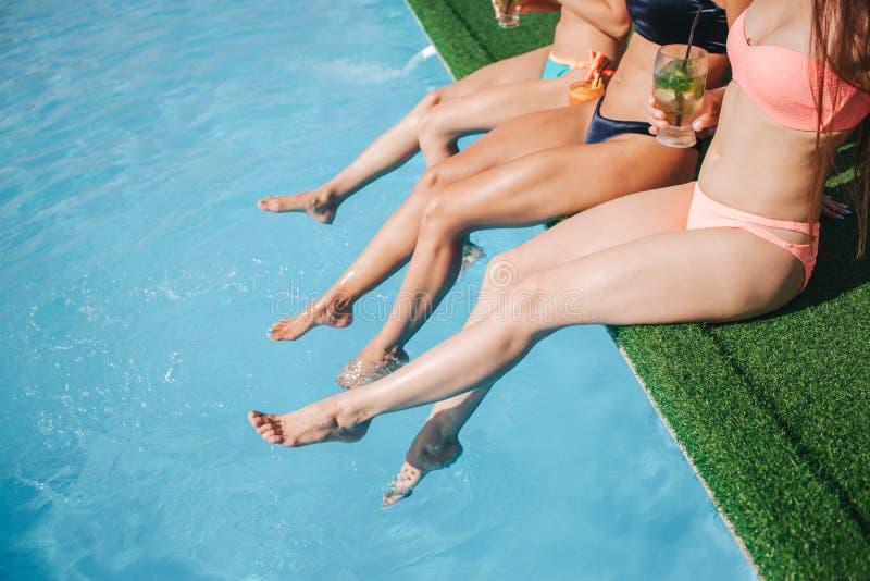 Coupez la vue des jambes modèles du ` s tenant des jambes dans l'eau et les éclaboussant dans la piscine Une femme a le cocktail  images stock
