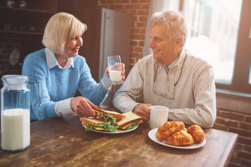 Coupez la vue des personnes supérieures s'asseyant dans la cuisine et le MI potable photo stock