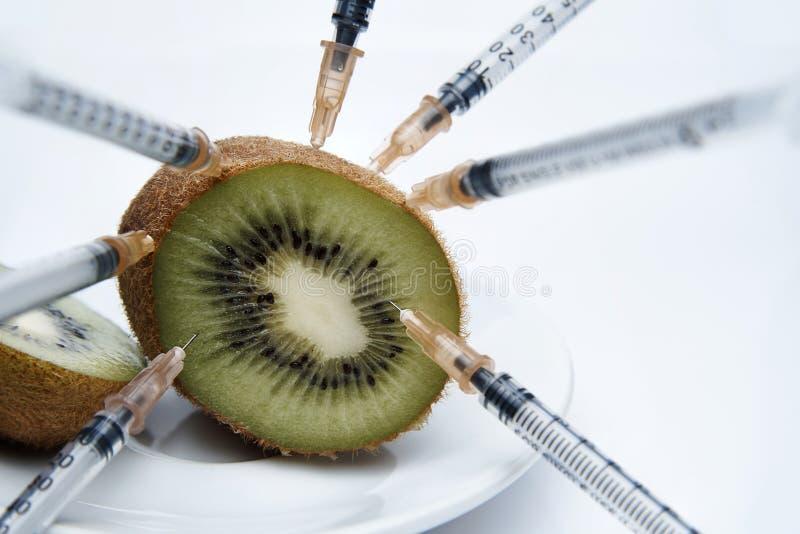 Coupez le kiwi avec les seringues injectées d'un plat blanc photos stock