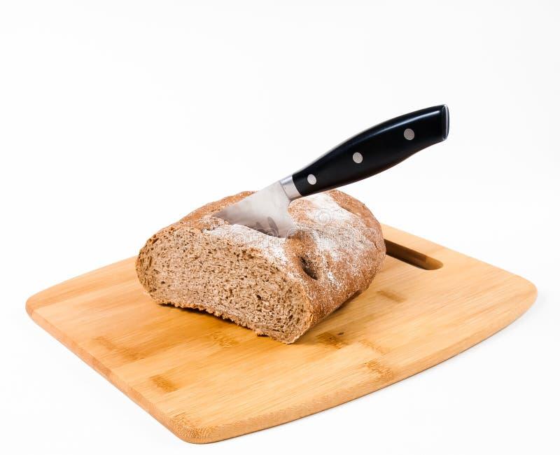 Coupez le pain noir sur la planche à découper images stock
