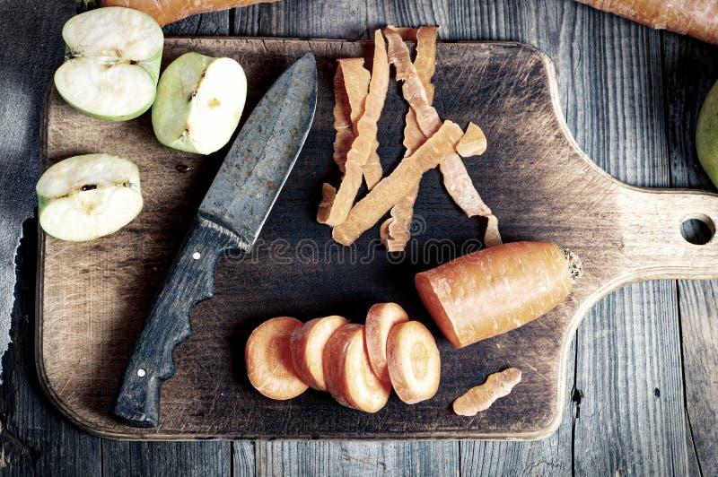 Coupez les carottes et avez coupé en tranches la pomme verte sur un panneau de cuisine photo stock