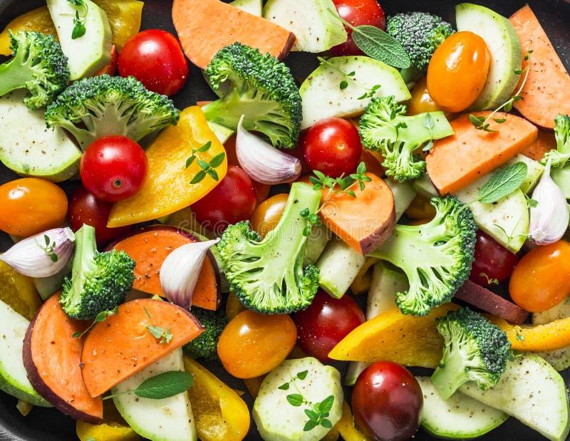 Coupez les légumes crus saisonniers - patates douces, brocoli, paprikas, courgette, tomates, oignons, ail avec des épices et herb images stock