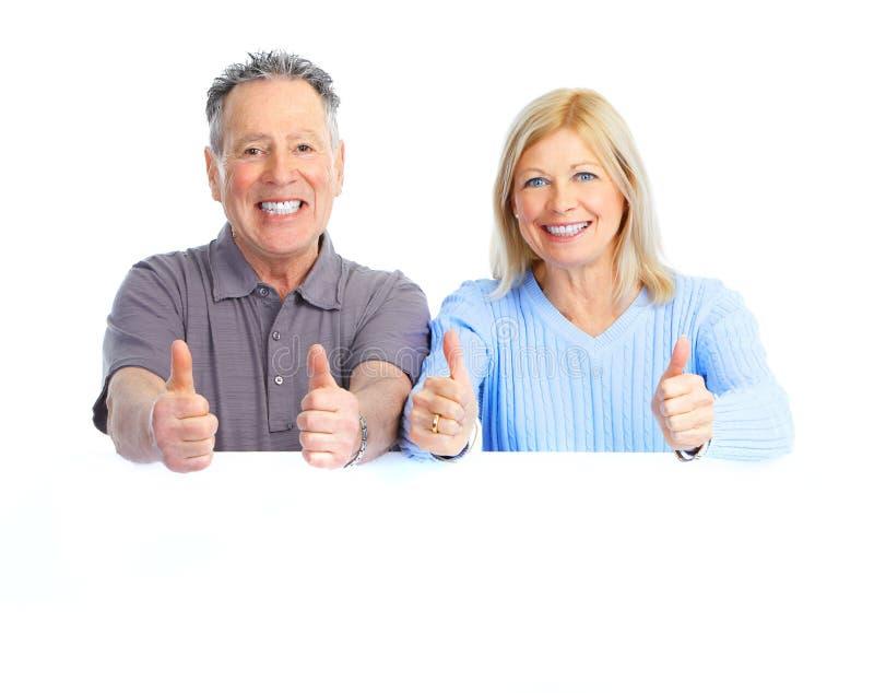 Couple. Happy seniors couple holding a white placard royalty free stock image