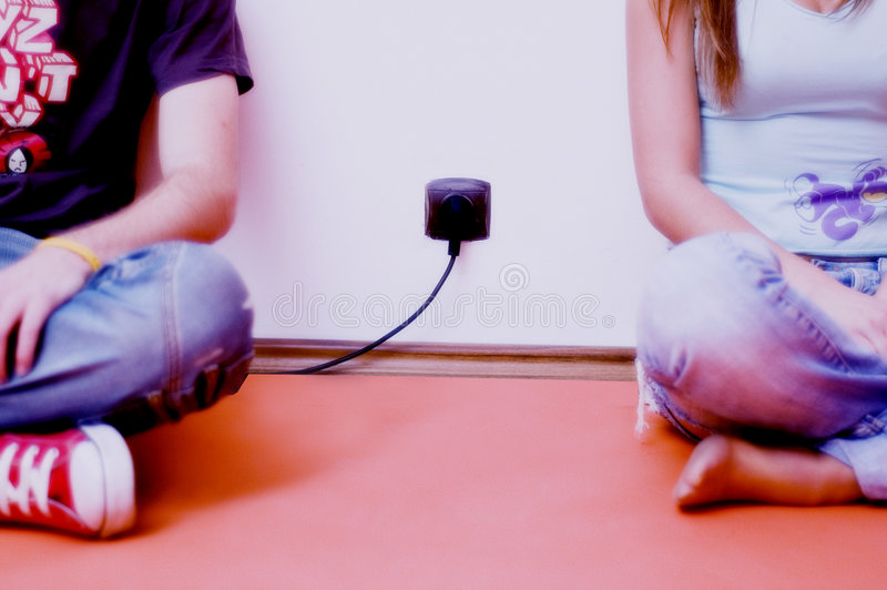 Couple. Boy and girl, sitting on floor crosslegged, seen from chest down, with electric outlet and plug between them royalty free stock photos