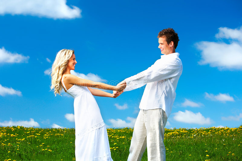 Couple. Young love couple smiling under blue sky stock photo