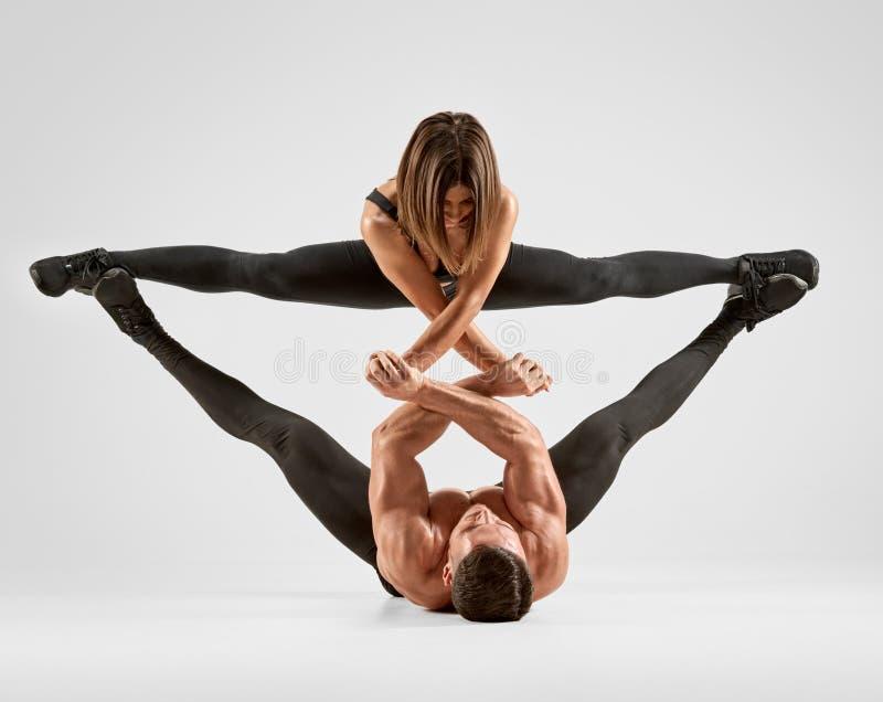 Couple Acrobatic gymnastics. Two young sporty gymnasts doing acrobatic elements royalty free stock image