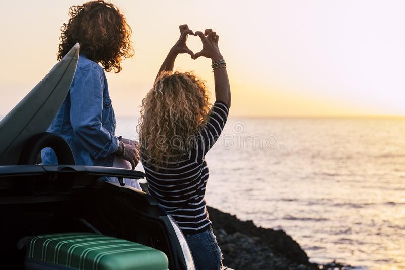 Couple of active young woman girls friends enjoy the summer sunset looking the ocean horizon together - curly blonde woman do stock images