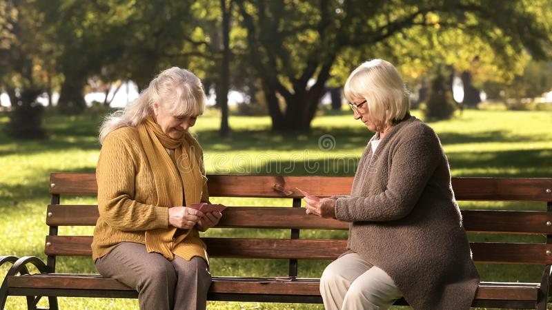 Couple of adult ladies playing cards sitting on bench in park, leisure activity royalty free stock photo